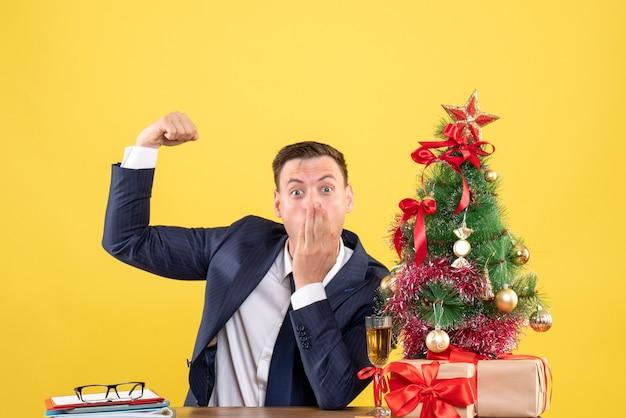 Vista frontal do homem espantado mostrando músculo sentado à mesa perto da árvore de natal e presentes sobre fundo amarelo