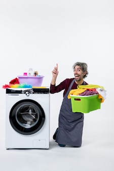 Vista frontal do homem exultante da governanta de pé sobre o joelho perto da máquina de lavar, segurando o cesto de roupa suja no fundo branco