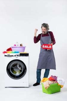 Vista frontal do homem exultante de avental segurando uma placa de venda em pé perto da máquina de lavar no fundo branco