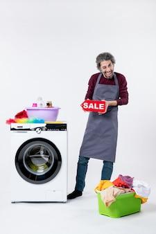 Vista frontal do homem exultante de avental segurando uma placa de venda em pé perto do cesto de roupa suja da máquina de lavar no fundo branco