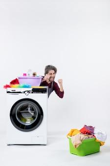 Vista frontal do homem exultante de avental sentado atrás do cesto de roupa suja da máquina de lavar roupa no fundo branco