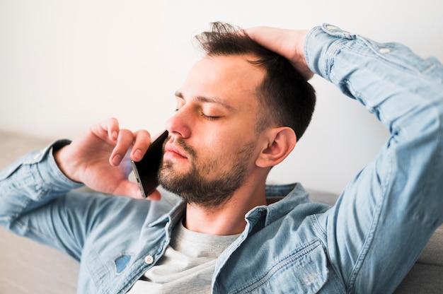 Vista frontal do homem falando no telefone