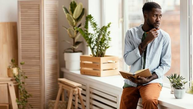 Vista frontal do homem fazendo planos para redecorar a casa