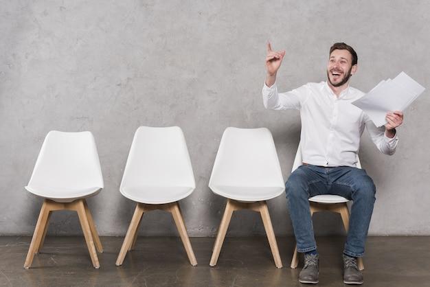 Vista frontal do homem feliz, à espera de sua entrevista de emprego