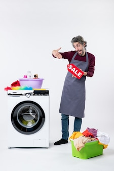 Vista frontal do homem feliz com avental segurando uma placa de venda em pé perto da máquina de lavar no fundo branco