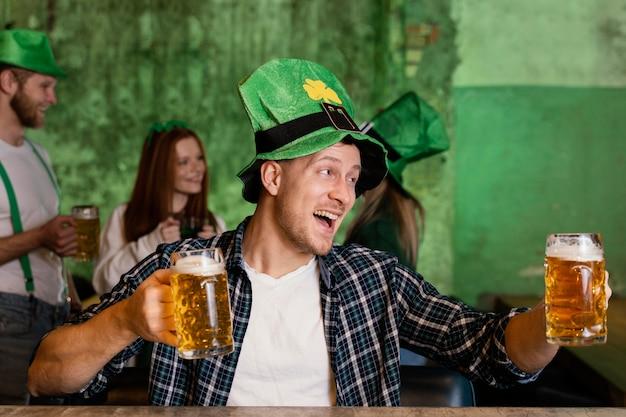 Vista frontal do homem feliz com chapéu comemorando st. dia de patrick com bebida no bar