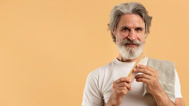 Vista frontal do homem idoso mais velho, segurando o pente