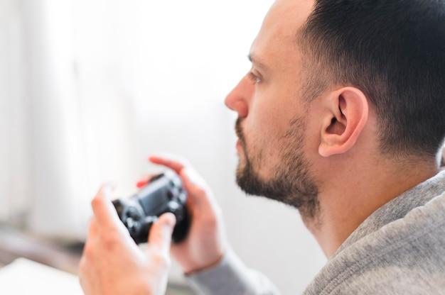 Vista frontal do homem jogando videogame