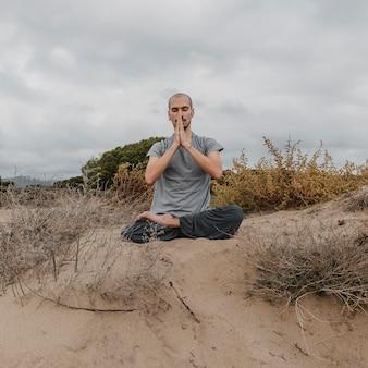 Vista frontal do homem lá fora relaxando enquanto faz ioga