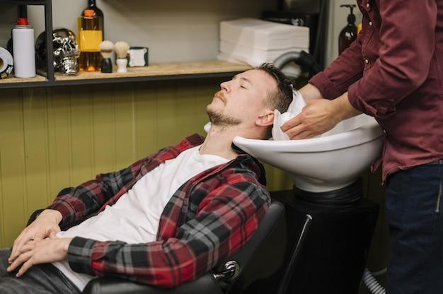 Vista frontal do homem lavando o cabelo na barbearia