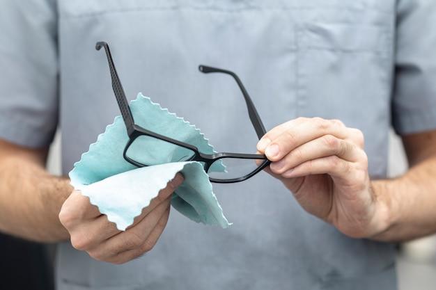 Vista frontal do homem limpando os óculos