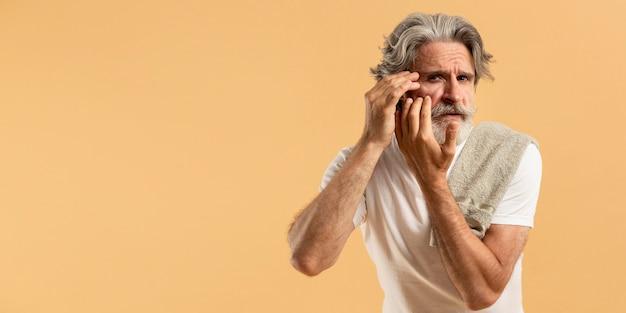 Vista frontal do homem mais velho com barba apontando rugas com espaço de cópia
