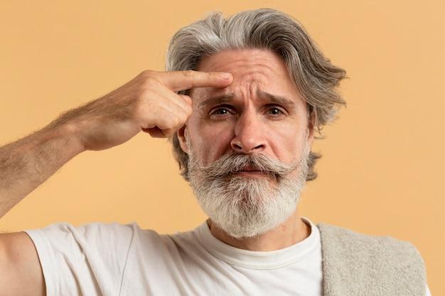 Vista frontal do homem mais velho com barba apontando rugas