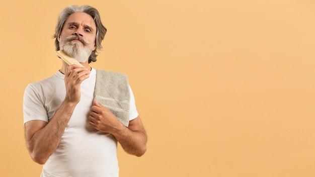 Vista frontal do homem mais velho com toalha, penteando a barba