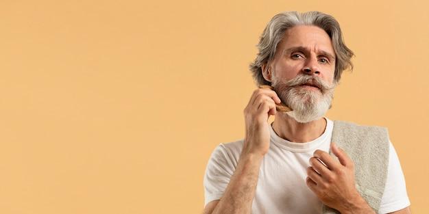 Vista frontal do homem mais velho, pentear a barba com espaço de cópia