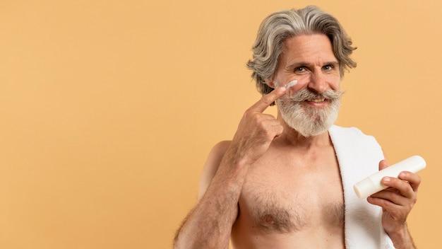 Vista frontal do homem mais velho sorridente com barba, aplicar creme no rosto