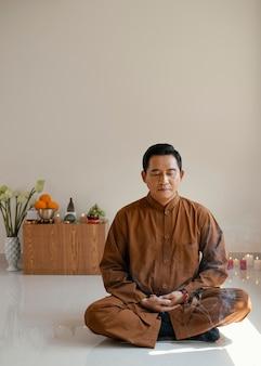 Vista frontal do homem meditando com espaço de cópia e incenso