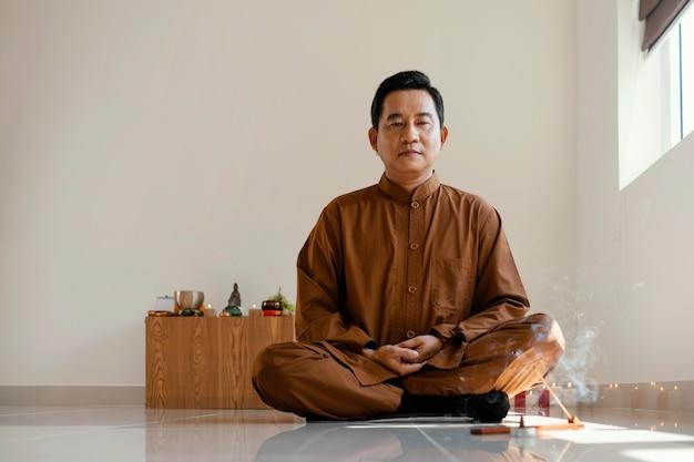 Vista frontal do homem meditando