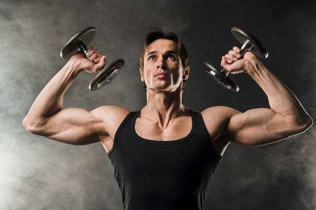 Vista frontal do homem musculoso, levantamento de pesos