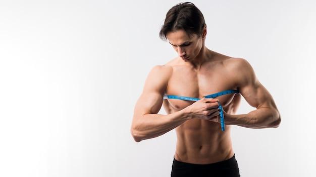 Vista frontal do homem musculoso, medindo o peito