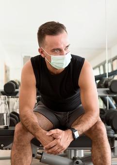 Vista frontal do homem na academia com máscara médica