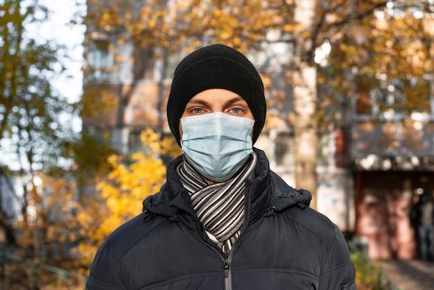 Vista frontal do homem na cidade com máscara médica