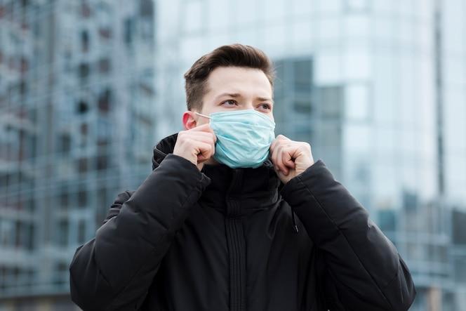 Vista frontal do homem na cidade usando máscara médica