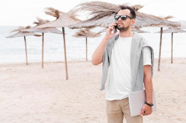 Vista frontal do homem na praia segurando laptop e falando no smartphone