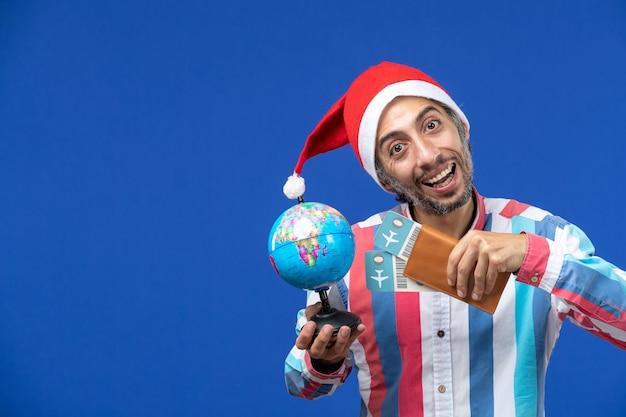 Vista frontal do homem normal com ingressos e globo na mesa azul, feriado de ano novo