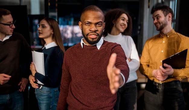 Vista frontal do homem oferecendo um aperto de mão após uma reunião
