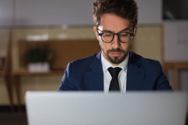 Vista frontal do homem pensativo em óculos digitando no laptop