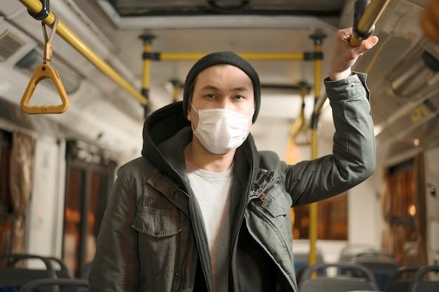 Vista frontal do homem posando com máscara médica no ônibus