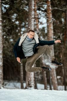 Vista frontal do homem pulando ao ar livre na natureza durante o inverno