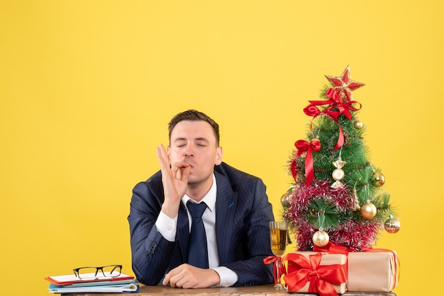 Vista frontal do homem satisfeito fazendo gesto de beijo do chef sentado à mesa perto da árvore de natal e presentes em amarelo
