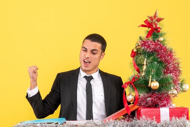 Vista frontal do homem satisfeito sentado à mesa mostrando o gesto vencedor, árvore de natal e presentes
