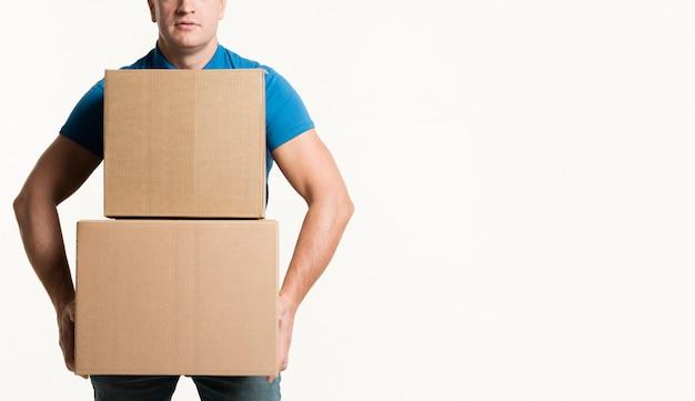 Vista frontal do homem segurando caixas de papelão com espaço de cópia