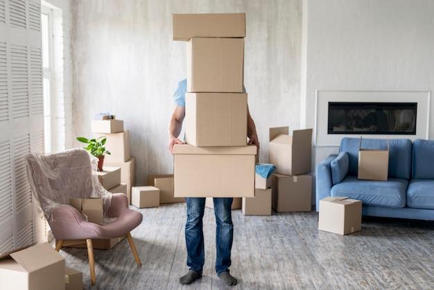 Vista frontal do homem segurando caixas enquanto se move, cobrindo o rosto