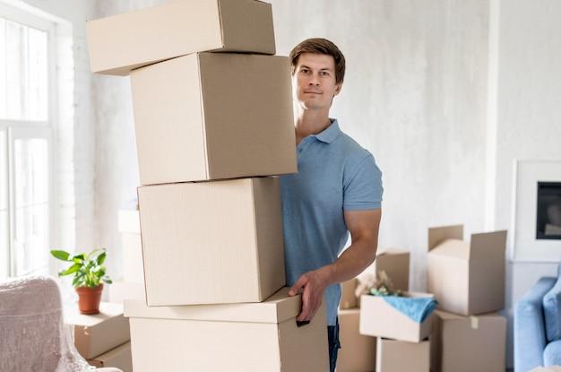 Vista frontal do homem segurando caixas para se mudar