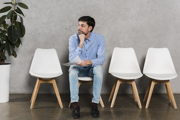 Vista frontal do homem segurando o currículo e esperando sua entrevista de emprego