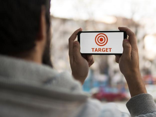 Vista frontal do homem segurando o smartphone com alvo