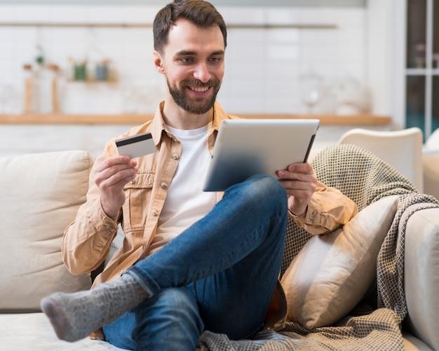 Vista frontal do homem segurando o tablet e cartão de crédito no sofá