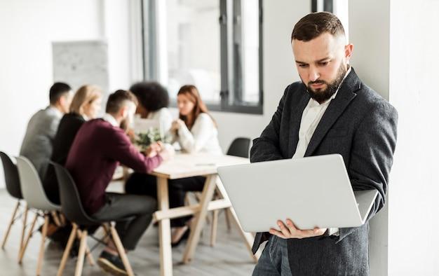 Vista frontal do homem segurando um laptop