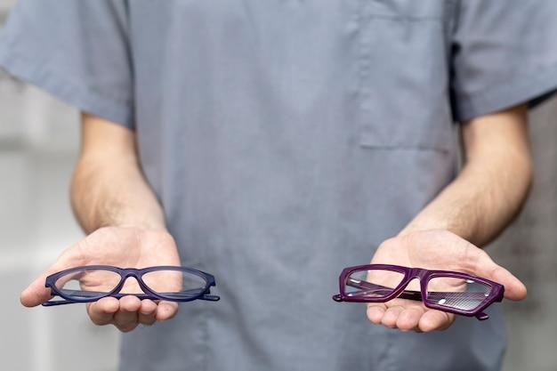Vista frontal do homem segurando um par de óculos em cada mão