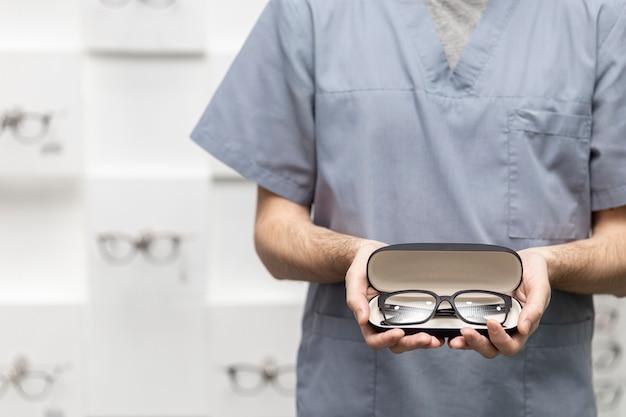 Vista frontal do homem segurando um par de óculos no caso