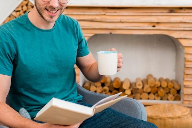 Vista frontal do homem segurando xícara e livro