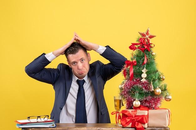 Vista frontal do homem sem alegria fazendo telhado da casa com as mãos, sentado à mesa perto da árvore de natal e presentes em amarelo