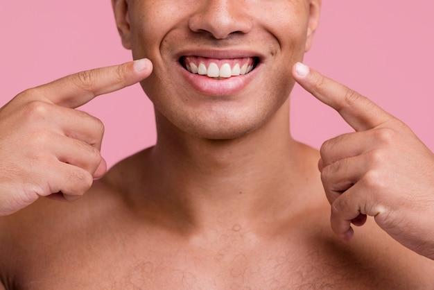 Vista frontal do homem sem camisa apontando para seu lindo sorriso