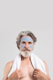Vista frontal do homem sênior com máscara facial e toalha