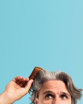 Vista frontal do homem sênior, penteando o cabelo