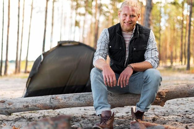 Vista frontal do homem sentado na árvore caída e na tenda atrás dele